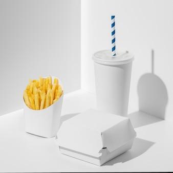 Упаковка для фаст-фуда под высоким углом с пустой чашкой и картофелем фри