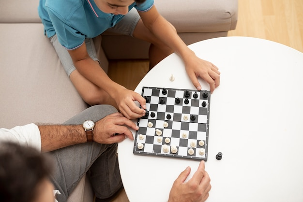 High angle father and child playing chess