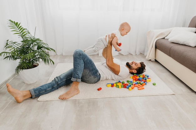 High angle of father playing on the floor with baby