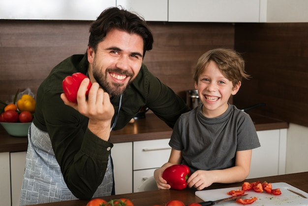 High angle father and son holding vegetables