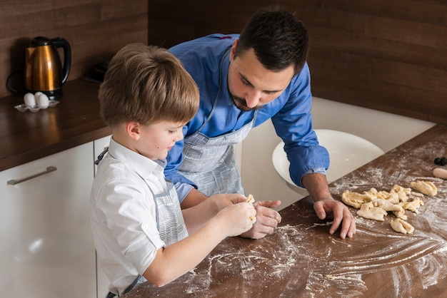 High angle father and son making shapes of dough