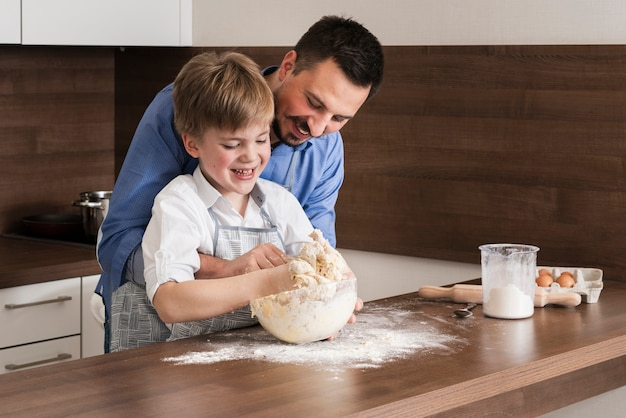 High angle father and son making together dough