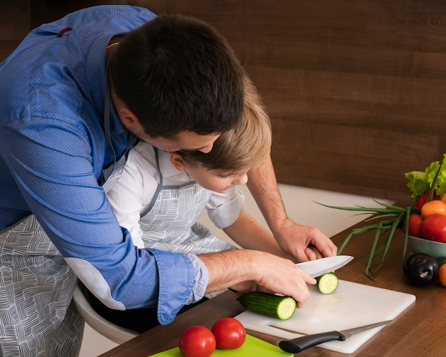 High angle father teaching son to cut vegetables