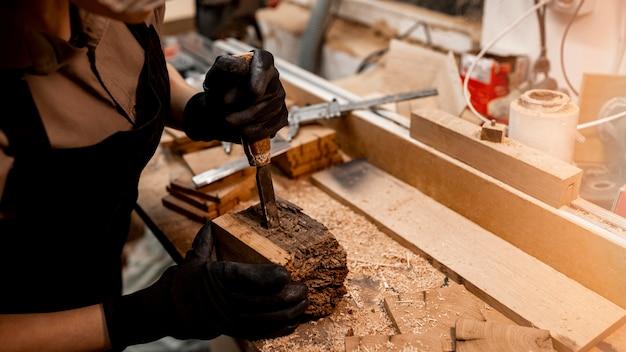 Alto angolo di falegname femminile in studio con strumenti per scolpire il legno