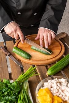 High angle of female chef cutting cucumbers