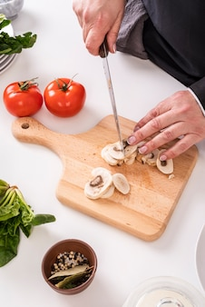 High angle of female chef cutting mushrooms