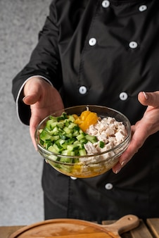 High angle of female chef holding bowl with ingredients
