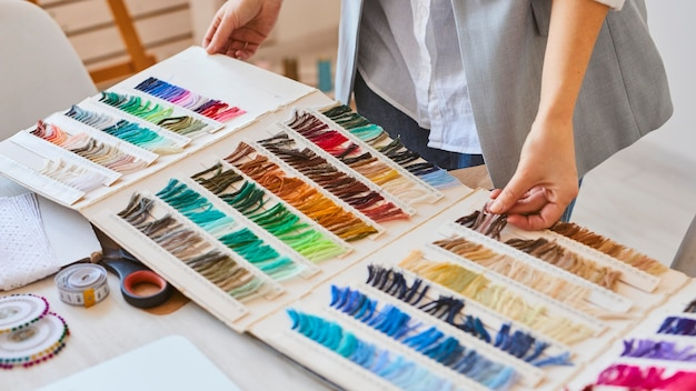 High angle of female fashion designer consulting color palette for clothing line