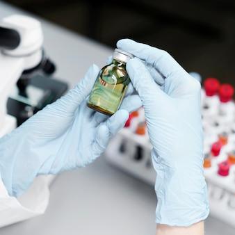 Alto angolo di ricercatore femminile in laboratorio con bottiglia di vaccino
