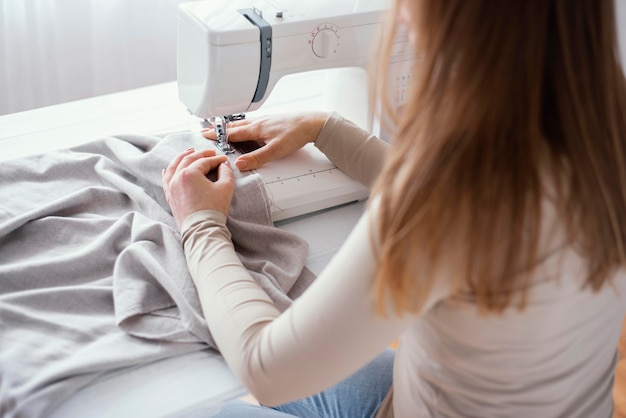 High angle of female tailor with sewing machine and fabric