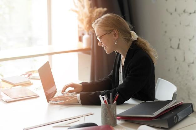 Учительница под высоким углом готовит урок на ноутбуке