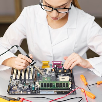 High angle of female technician with electronics and soldering iron