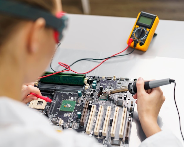 High angle of female technician with soldering iron and electronics motherboard