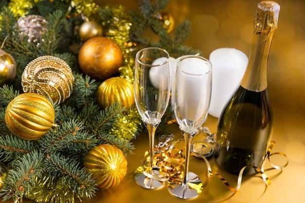 金のボールとキャンドルで飾られた常緑の枝と黄色の背景にシャンパンのボトルとエレガントなメガネのペアのハイアングルお祝いクリスマス静物