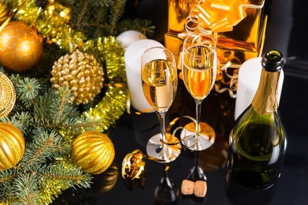 ハイアングルのお祝いの静物-黒い背景にボトル、キャンドル、ギフト、クリスマスの装飾が施されたスパークリングシャンパン2杯