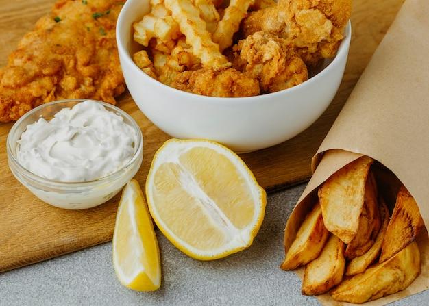 Alto angolo di fish and chips nella ciotola e avvolgere la carta con il limone