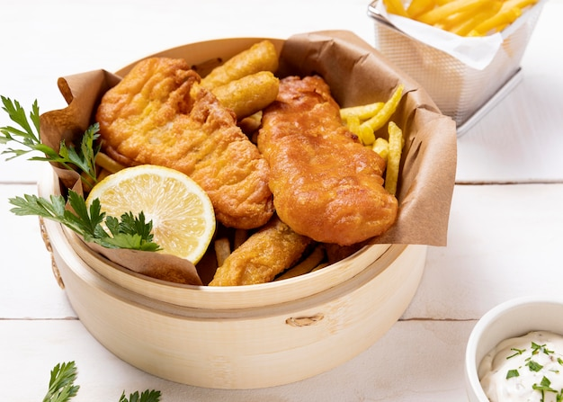 High angle of fish and chips in bowl with lemon