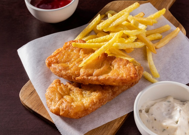 High angle of fish and chips on chopping board with sauces