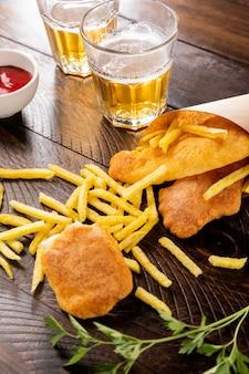Alto angolo di fish and chips nel cono di carta con la birra