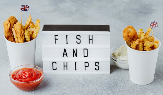High angle of fish and chips in paper cups with great britain flags and light box