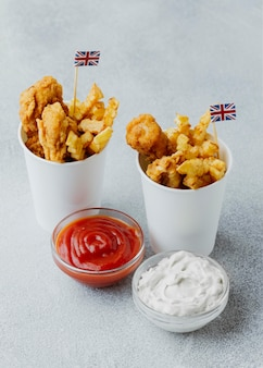 High angle of fish and chips in paper cups with great britain flags and sauces