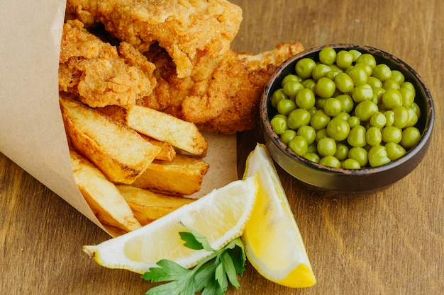 High angle of fish and chips in paper wrap with peas and sauce