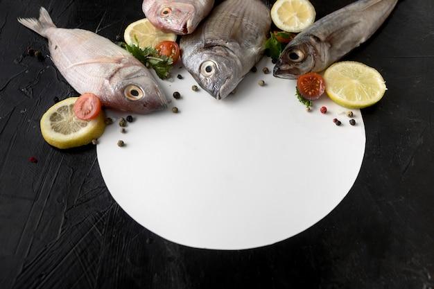 High angle of fish with plate and lemon