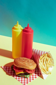 High angle food arrangement with sauce bottles and burger