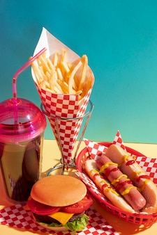 High angle food assortment with juice cup and cheeseburger