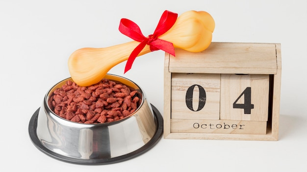 High angle of food bowl with bone and wooden calendar for animal day