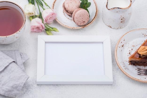 High angle of frame with tea and macarons