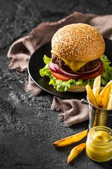 Свежий бургер под высоким углом, картофель фри и соус