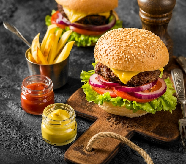 High angle fresh burgers on cutting board with fries and sauces