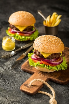 High angle fresh burgers on cutting board with fries