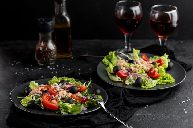 High angle fresh meal with dark tableware and wine glasses