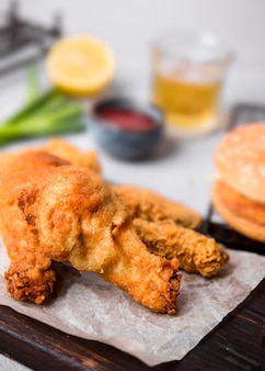 High angle fried chicken on cutting board with burger