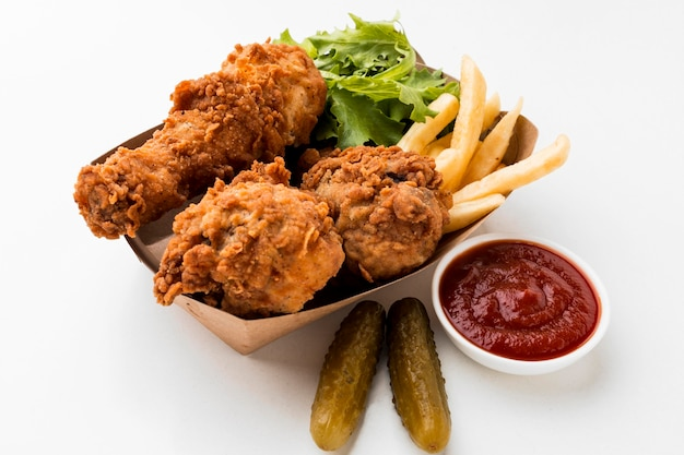 High angle fried chicken drumsticks with ketchup and fries