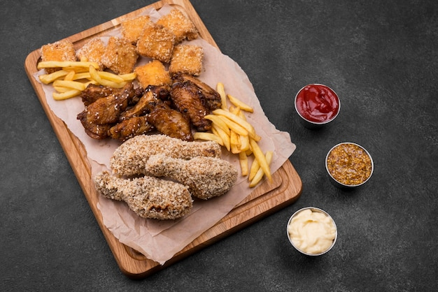 High angle of fried chicken and french fries on chopping board