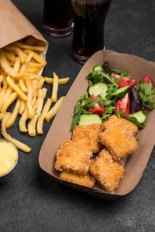 High angle of fried chicken nuggets with french fries and salad