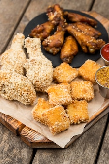 Angolo alto di bocconcini di pollo fritto con varietà di salse
