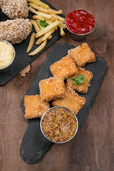 High angle of fried chicken on slate with french fries and sauce