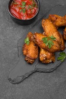 Alto angolo di pollo fritto su ardesia con salsa