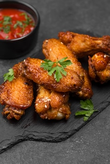 High angle of fried chicken wings on slate with sauce