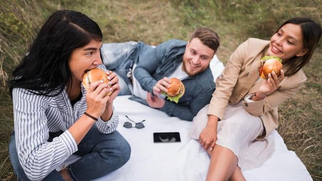 Amici di alto angolo che mangiano hamburger