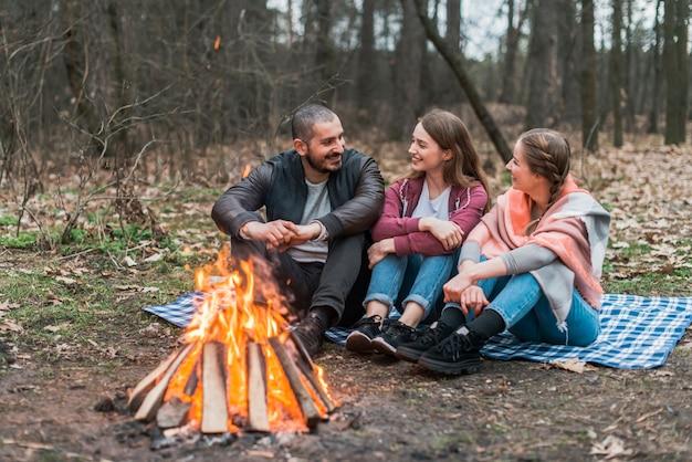 High angle friends talking at bonfire