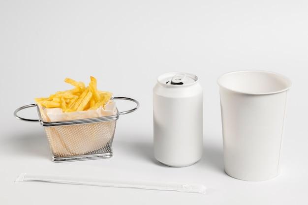 Картофель фри под высоким углом с пустой банкой из-под газировки и чашкой