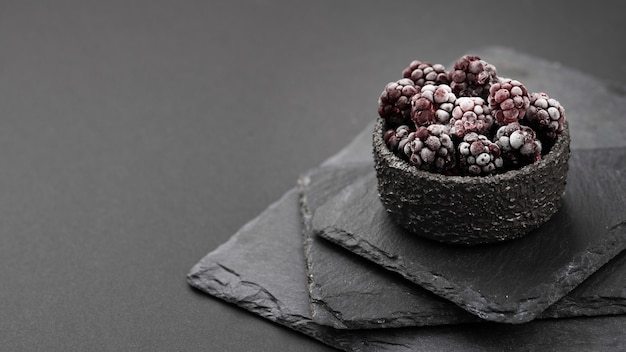 High angle of frozen blackberries in bowl with slate