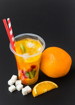 High angle of fruit juice in cup with straws
