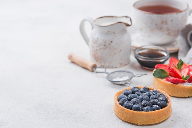 High angle of fruit tarts with copy space and tea