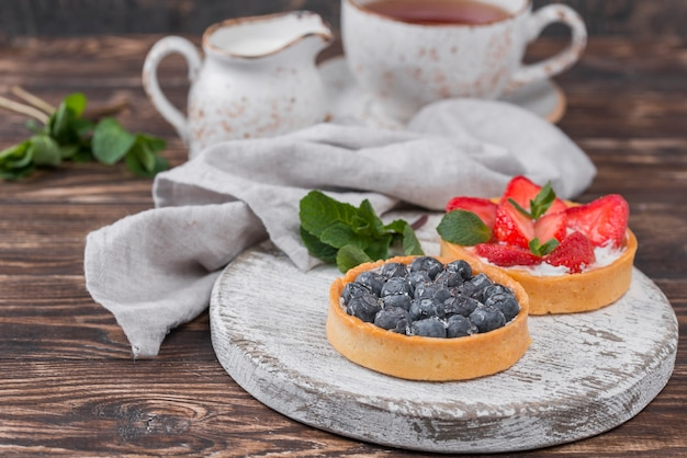 High angle of fruit tarts with mint and tea